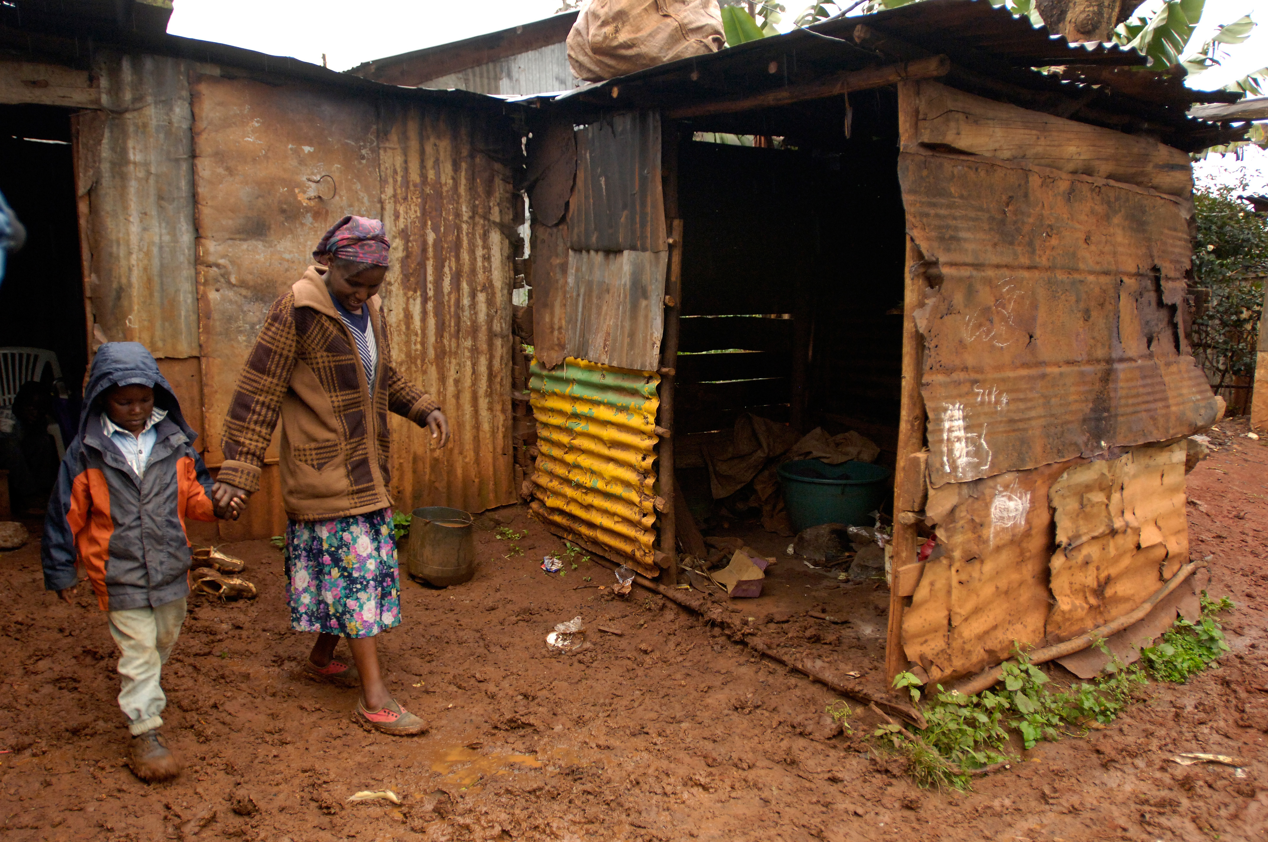 Boy with mother walking on wet ground from shack