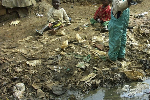 Children playing over an open sewer in Kibera
