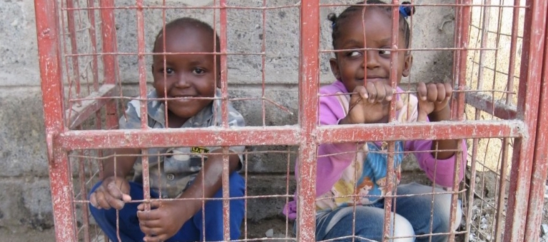 Two children sitting in a metal cage