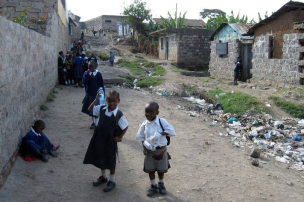 Queue of school children near a line of rubbish